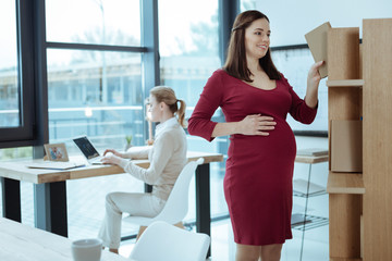 Working atmosphere. Beautiful pregnancy keeping smile on her face and touching belly while standing on the foreground