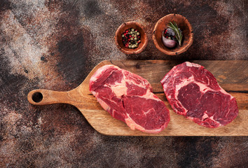 Wall Mural - Two raw ribeye steaks on a cutting board, garlic, rosemary and pepper. Top view
