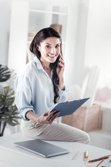 Look at me. Cheerful brunette holding folder in right hand, looking at camera