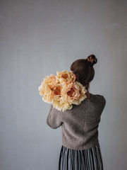 Woman holding peonies over her shoulder