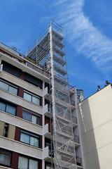 Échafaudage métallique le long d'un immeuble, ciel bleu