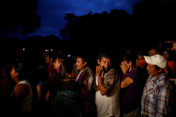 Evacuees queue for free ice-cream in a provisional shelter after the eruption of the Fuego volcano damaged their community in Escuintla