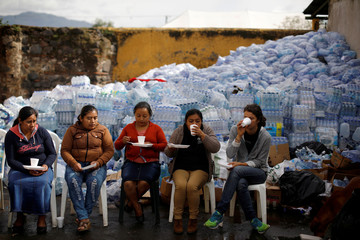 Women drink coffee at a collection centre at an area affected by the eruption of Fuego volcano in Alotenango