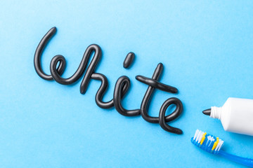 Black toothpaste from charcoal for white teeth. Word WHITE from  black toothpaste,  tube and toothbrush on  blue background.