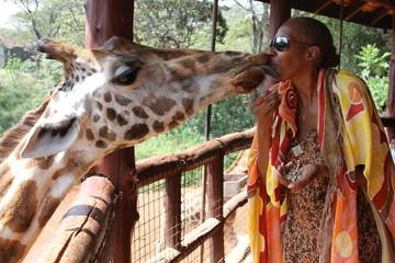 Woman kissing a giraffe