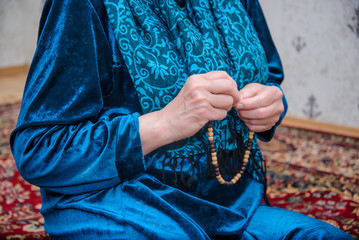 Women's hands are sorting out Muslim prayer beads