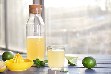Fresh citrus drink in glassware and lime on table