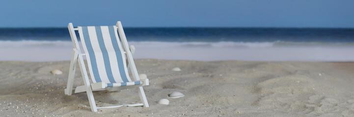 Blue white striped deck chair on the beach, panorama