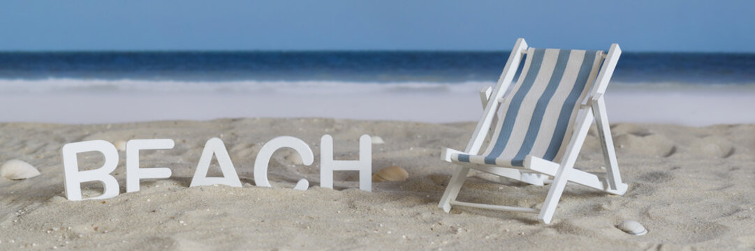 The word beach in white wooden letters in the sand on the beach, beside a deck chair