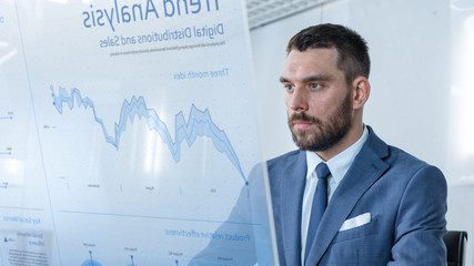 In the Near Future Successful Businessman Works on Computer with Transparent Display that Shows Trend Analysis, Numbers, Rises and Downs.