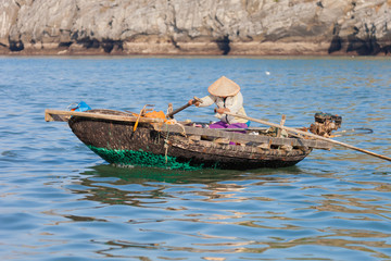 Ha Long Bay, Vietnam-December 18, 2015. Vietnamese woman rowing traditional bamboo boat on December 18, 2015 at Ha Long Bay of north Vietnam.