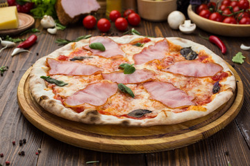 Delicious italian pizza with ham and basil leaves on wooden background