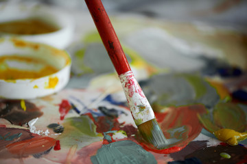 Close up of color palette. Mixed colors and paint brushes in focus.