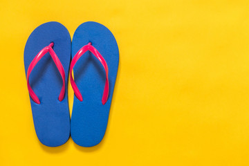 Travel vacation background. Flip flops on a yellow background. Flat lay