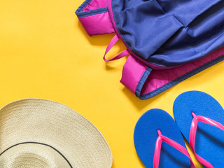 Travel vacation background. Flip flops, backpack, hat on a yellow background. Flat lay
