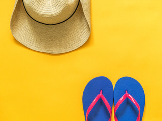 Travel vacation background. Flip flops, hat on a yellow background. Flat lay