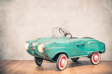 Fond de hotte en verre imprimé Vintage voitures Retro outdated rusty metal turquoise pedal car toy from circa late 60s or early 70s in front concrete textured wall background. Vintage style filtered photo