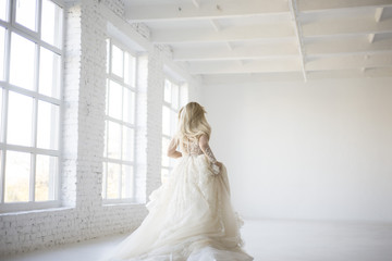 bride run and dance in her wedding dress in big white room with big windows