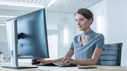 Beautiful Creative Woman Working on the Computer in the Bright Modern Office. She Has Short Hair and Wears Cosmic Gray Dress.