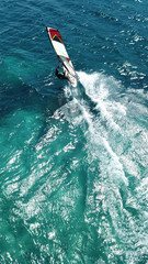 Aerial drone bird's eye view photo of competition surfers in tropical wavy clear waters
