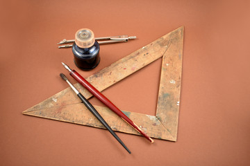 Old art tools stock images. Old tools for drawing. Vintage painting tools on a brown background. Art supplies images