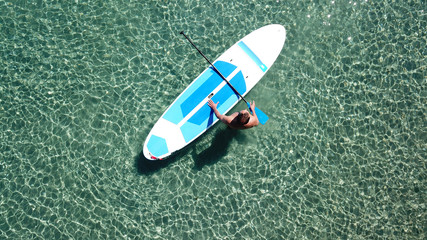 Aerial drone bird's eye view of a man exercising sup board in turquoise tropical clear waters at sunset