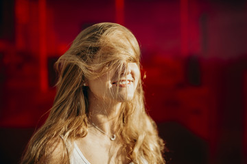 Smiling blonde girl with long hair moving around her face.