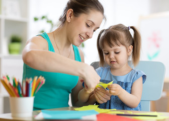 Mother helping her child daughter to cut colored paper