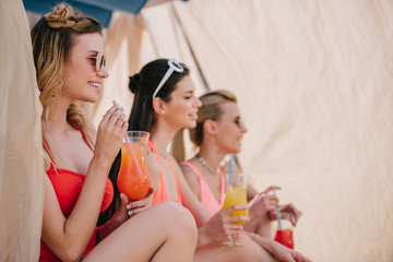 side view of smiling girls in swimwear drinking cocktails and looking away in bungalow on beach