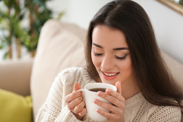 Beautiful young woman with cup of hot tea at home