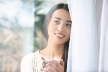 Beautiful young woman with cup of hot tea at home, view through window