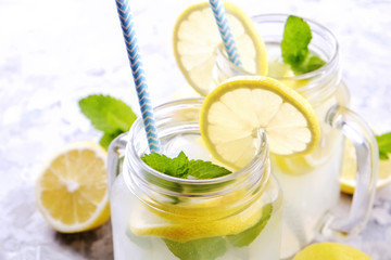 Two mason jar glasses of homemade refreshing lemonade with slices of organic ripe lemon, whole and halved, mint, ice cube on grunged grey concrete table background. Close up, top view, copy space.