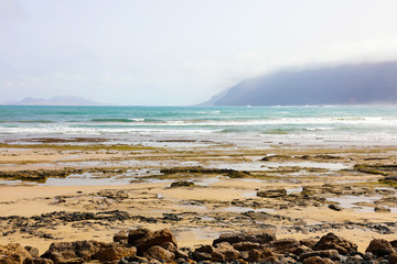 This picture was taken from Caleta Famara beach on Lanzarote Island, on the background you can see La Graciosa Island and mountains with fog