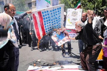 Iranians burn a cloth in the likeness of the U.S. flag and an image of Israel's Prime Minister Benjamin Netanyahu during a protest marking the annual al-Quds Day (Jerusalem Day) on the last Friday of the holy month of Ramadan in Tehran, Iran