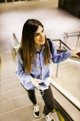 Portrait of smiling young woman standing on escalator listening music with cell phone and earphones