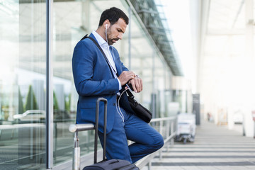 Businessman at airport, looking on watch