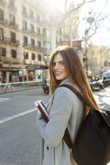 Spain, Barcelona, portrait of smiling young woman with backpack standing at street