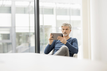 Mature man sitting in his office, using digital tablet
