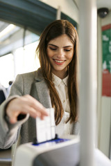 Portrait of smiling young woman validating ticket in tramway