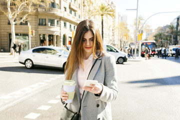 Spain, Barcelona, young woman with coffee to go standing at roadside looking at cell phone