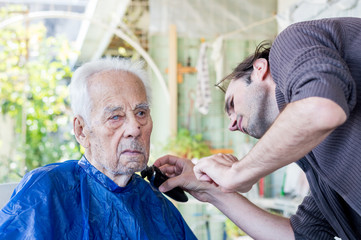 Old man getting his beard shaved by young skilled man at home