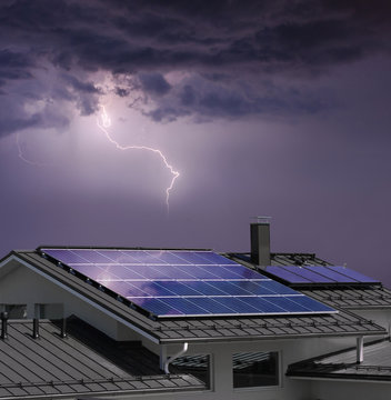 House with solar panels in thunderstorm