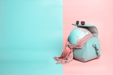 Travelling globe going on vacation in travel bag with sunglasses and scarf on soft pink and light mint pastel colored background, Copy space, Trendy vanilla colors