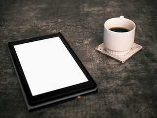 Blank screen tablet mock up on a wooden surface and a cup of coffee on the side