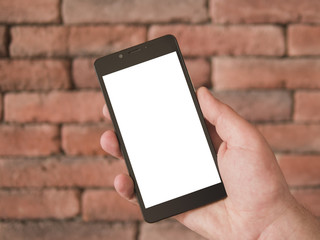 Mock up image of hand holding black mobile phone with blank white screen in portrait mode on a brick wall background