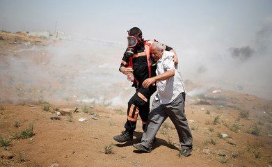 Palestinian demonstrator is evacuated after inhaling tear gas fired by Israeli troops during a protest marking al-Quds Day, (Jerusalem Day), at the Israel-Gaza border, east of Gaza City