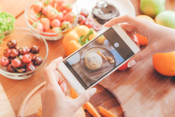 woman holding smart phone take a photo of food on table.