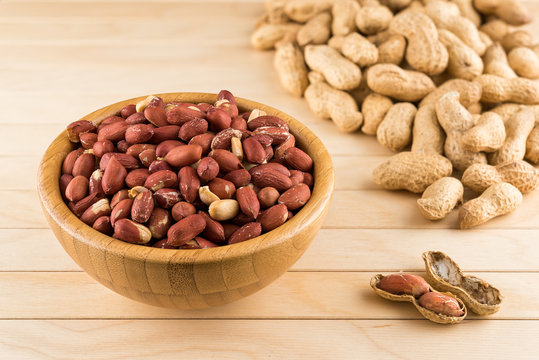 Wooden bowl full of peeled peanuts and peanuts in nutshell on a wooden table
