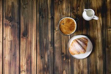 Homemade croissant with sugar powder, cup of coffee, jug of milk over wooden plank background. Flat lay, space.