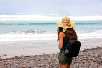 Back view of backpacker female with straw hat looking to La Graciosa Island from Caleta Famara beach, Lanzarote, Spain